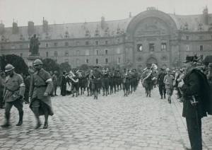 Après la cérémonie dans la cour d'honneur, la musique américaine défile sur l'esplanade, devant la façade nord, suivie par le cortège officiel. Au dessus du porche permettant d'accéder à la cour, les trois grandes fenêtres de la salle d'honneur sont ouvertes. Il semble que plusieurs personnes soient montées sur le toit du pavillon central, au-dessus du bas-relief représentant Louis XIV à cheval, pour assister au défilé. © Paris, musée de l'Armée