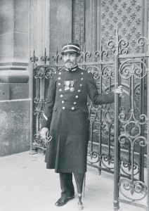 Georges Hector Dumont (1856-1930), gardien du tombeau de l'Empereur, devant le portail du Dôme des Invalides, vers 1910-1912. Il tient la clef du Dôme dans sa main gauche et porte une épée sur sa hanche gauche. © Paris, musée de l'Armée