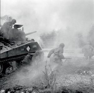 Les nouvelles recrues FFI incorporées dans la 1re armée française s'entraînent à accompagner les chars.  L'infanterie portée saute du char en marche et va franchir le ruisseau, protégée par un écran fumigène, Alsace, 1er-12 mars 1945 © ECPAD / Jacques Belin