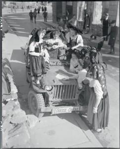 Jeunes Alsaciennes en costume traditionnel autour d'une jeep du service Presse Cinéma du SCA. D'après la légende d'origine, elles sont en train de lire une carte les noms des villes libérées, Alsace, 18 mars 1945 © ECPAD / Jacques Belin