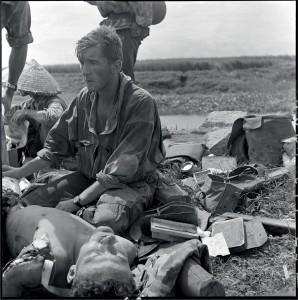 Le médecin lieutenant Patrice de Carfort, du 8e bataillon de parachutiste de choc (BPC), porte assistance au sergent Camille Lambert, mourant suite à l'explosion d'une mine à Cad Khe. CE dernier décède le 28 septembre 1953, Indochine, 24-28 septembre 1953 © ECPAD / Pierre Ferrari