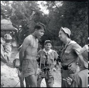 """Opération """"Toulouse"""", dans la région de Binh Dinh et Qui Nhon. Un capitaine interroge un prisonnier viêt-minh dont le cou est enserré d'une épaisse ficelle, Indochine 29 janvier - 6 février 1953 © ECPAD / Paul Corcuff"""