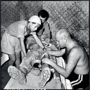 """À l'antenne chirurgicale souterraine du sud de Diên Biên Phu, le médecin commandant Paul Henri Grauwin, dit """"Toubib"""", soigne un blessé. Il opère pendant 54 jours, plus de quatre mille blessés, 27 mars 1954 © ECPAD / Daniel Camus / Jean Péraud"""