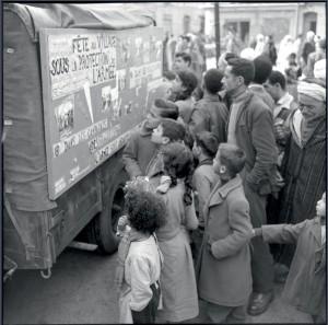 """Opération """"Cisailles"""" à Oran : le panneau d'information d'un camion de l'action psychologique retient l'attention des riverains, 24 novembre 1957 © ECPAD / Marc Flandrois"""