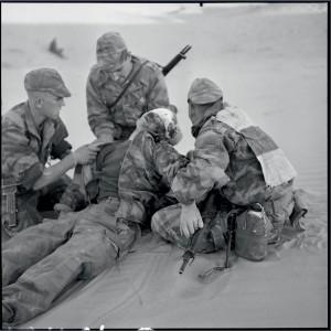 Bataille de Timimoun : mortellement blessé au combat, le jeune parachutiste Jacques Schneidenbach, âgé de vingt ans est entouré par ses camarades du  RPC, Hassi-Rhambou, Algérie, 21 novembre 1957 © ECPAD / Marc Flament