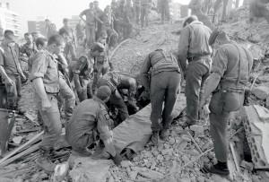 Le corps d'une victime de l'attentat du poste Drakkar a été trouvé dans les décombres. La dépouille est sur le point d'être emmenée sur un brancard afin de procéder à l'identification puis à la mise en bière, Beyrouth, 25 octobre 1983 © ECPAD / Joël Brun
