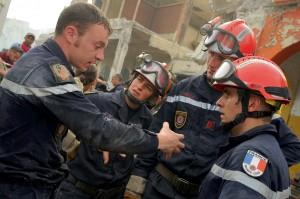 Un sauveteur de la sécurité civile raconte à ses collègues comment il a pu atteindre la main du rescapé sous les décombres de l'hôtel, Port-au-Prince, 23 janvier 2010 © ECPAD / Caporal-chef Jérôme